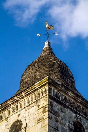 gusty: A golden wind vane above a church in the sunshine