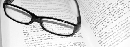 A close up shot of glasses on a book photo