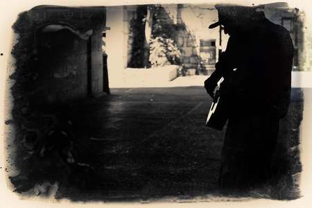 vagabond: A Man playing guitar in an alley