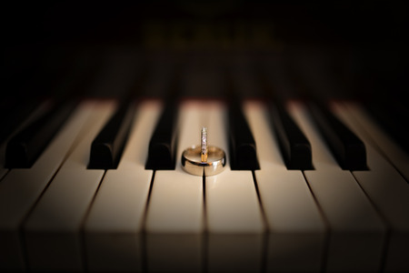 Artistic shot of wedding rings on old piano photo