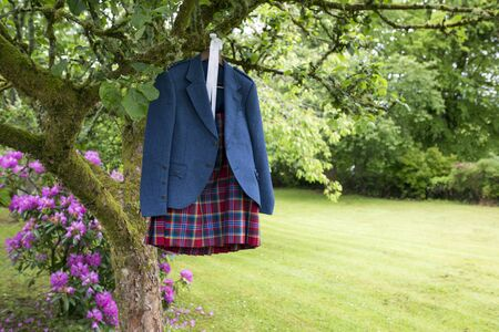 scot: shot of a Wedding Kilt Hanging on wooden frame