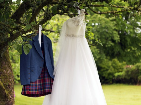 kilt: Shot of a Kilt and wedding dress hanging on a tree Stock Photo