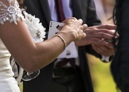 Shot of a bride choosing a card from a magician at a wedding Standard-Bild