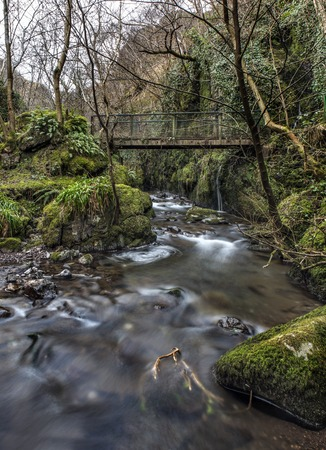 Shot of a river flowing under an old bridge