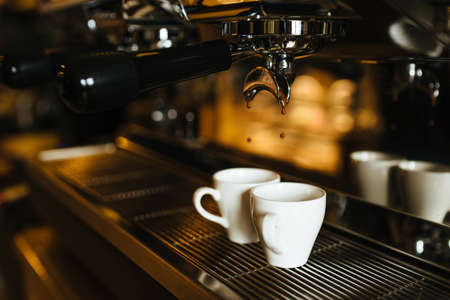 The moment of the brewing process of espresso. Coffee pours into two white cups. Stock Photo