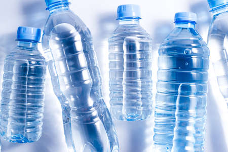 Several plastic water bottles on white background. The concept of plastic free pattern