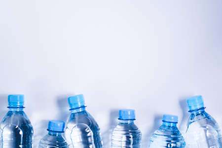 Several drinking water bottles on white background. Eco concept. Copy space for your text. Banco de Imagens