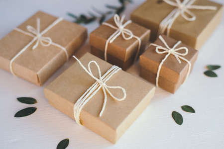 Craft gift boxes on white wooden background.