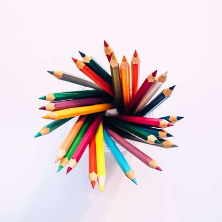 Colored pencils in a glass on a white background. The view from the top. Copy space