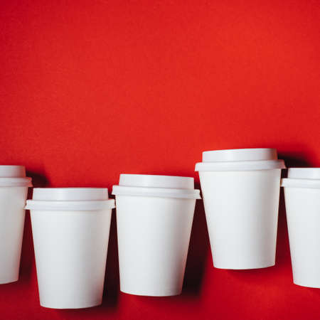 Several paper cups for coffee or tea on red background. Copy space for text. Imagens