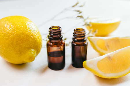 Two bottle of lemon essential oil on white background for beauty, skin care, wellness and medicinal purposes.