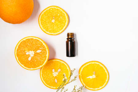 Bottle of orange essential oil on white background for beauty, skin care, wellness and medicinal purposes. Flat lay.