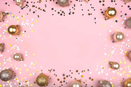 Festive pink background with gold and silver stars and Christmas balls. Flat lay, top view. Copy space for your text.