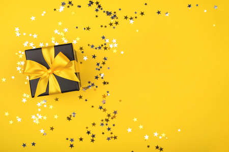 Black gift box with yellow bow on yellow background with sparkling confetti. Flat lay. Copy space. Zdjęcie Seryjne