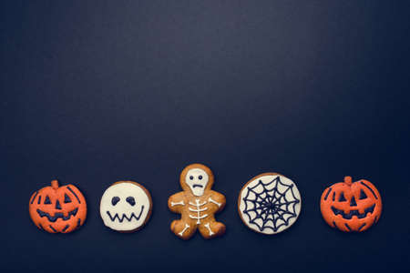 Halloween gingerbread cookies on dark background. Flat lay. Copy space for your text.