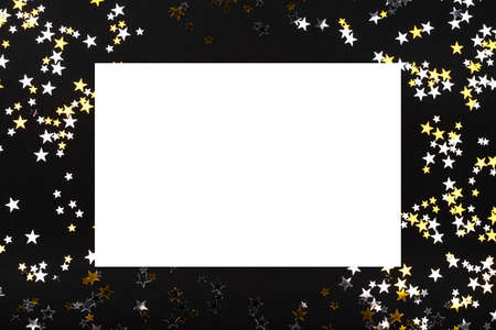 Golden and silver stars on black background. Flat lay, top view. Holiday concept. Copy space for your text.