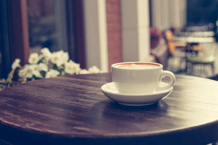 View of a summer terrace cafe with cup of cappuccino on the table.