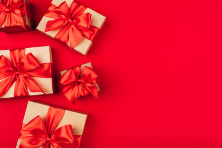 Frame of cardboard gift boxes with bows on red background. Flat lay, top view. Copy space for text.