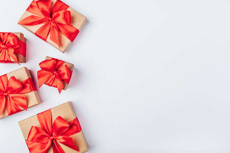 Frame of cardboard gift boxes with red bows on white background. Flat lay, top view. Copy space for text.