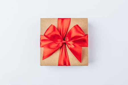 Cardboard gift box with red bow on white background. Flat lay. Top view.