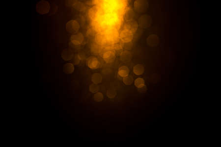 Golden abstract bokeh on black background. Holiday concept.