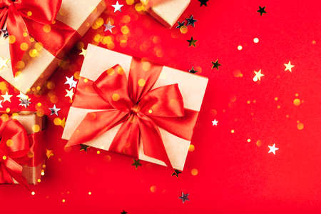 Several gift boxes with bows on a red background with lights and confetti in the shape of stars. Holiday concept.