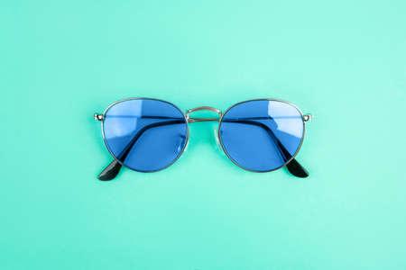 Blue sun-glasses on mint background. Color of year 2020. Standard-Bild - 134823498