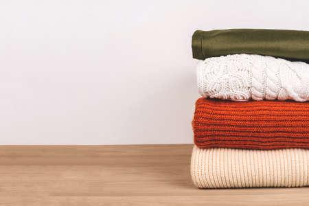 Montón de ropa de abrigo sobre la mesa. Colores Primavera-Verano 2020. Copie el espacio para el texto.