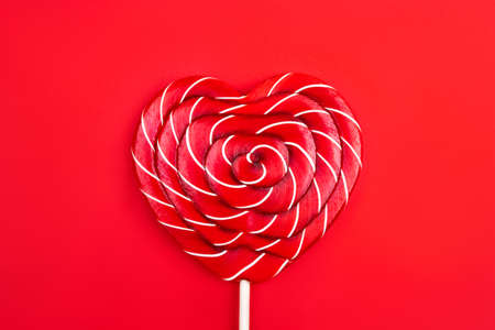 A heart-shaped lollipop on a red background. Valentine's Day concept. Flat lay, top view.