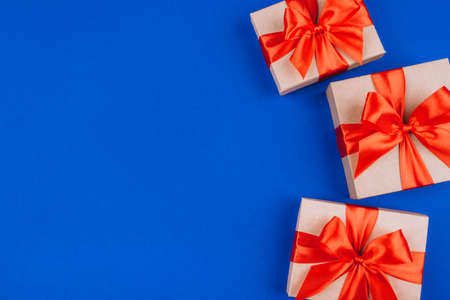 Frame of cardboard gift boxes with bows on blue background. Flat lay, top view. Copy space for text.