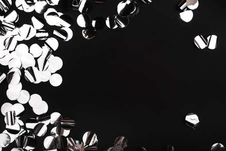 Silver confetti on black background.. Flat lay, top view. Copy space.