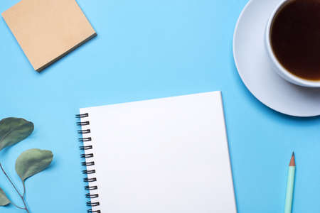Blauer Hintergrund mit Notizblock, Bleistift und Tasse Kaffee. Draufsicht mit Kopienraum, flache Lage.