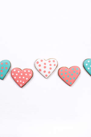 Gingerbread cookies with frosting in the shape of a heart on white background. Valentines day concept. Flat lay, top view.