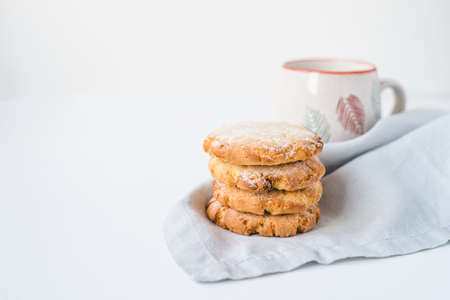 Stacked cookies on a linen napkin and a cup of coffee. Close up.