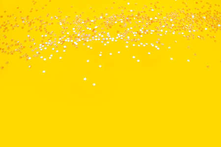 Tiny pearl stars on yellow background. Flat lay, top view.