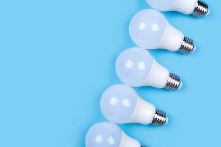 Several LED bulb on blue background. Saving energy concept. Ftat lay, top view, copy space.