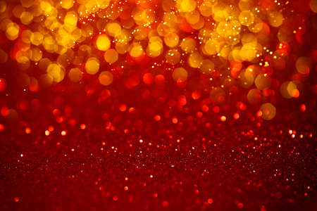 Red shiny festive abstract background with golden lights. Defocused sequin light.