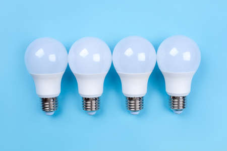 Four LED bulbs on blue background. Saving energy concept. Ftat lay. Top view. 스톡 콘텐츠