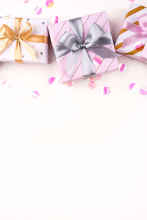 Gift boxes with bows and confetti on a white background. Flat lay composition. Birthday, christmas, wedding or another holiday concept.