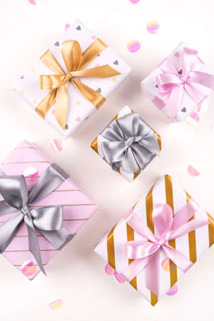 Set of gift boxes with bows and confetti on a white background. Flat lay composition. Birthday, christmas, wedding or another holiday concept.