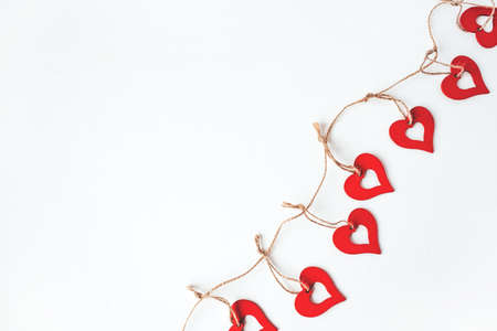 Valentines day decoration with ornaments in the form of hearts. White wooden background.