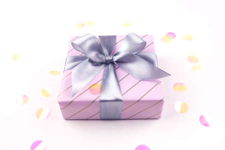 One gift boxe with bow and confetti on a white background. Flat lay composition. Birthday, christmas, wedding or another holiday concept.