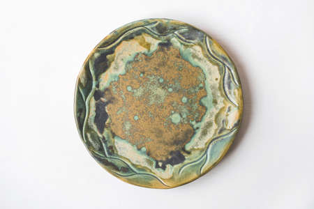 Handmade ceramics in the style of wabi sabi. Green clay plate with an abstract pattern.