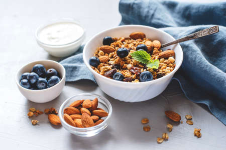 Baked granola with yogurt and blueberries on a gray table. Stockfoto
