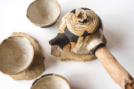 Handmade ceramics in the style of wabi sabi. Brown clay teapot and cups with an abstract pattern. Stock Photo