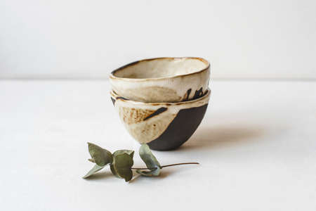 Handmade ceramics in the style of wabi sabi. Brown clay bowls with an abstract pattern. Stock Photo
