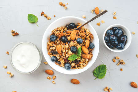Baked granola with yogurt and blueberries on a gray table. Top view.
