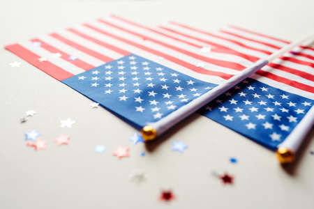 Festive background with US flags and confetti in the shape of stars. US independence day.