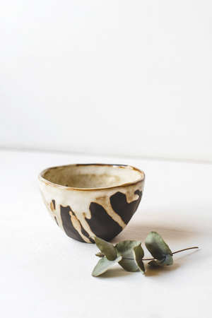 Handmade ceramic in the style of wabi sabi. Brown clay bowl with an abstract pattern.