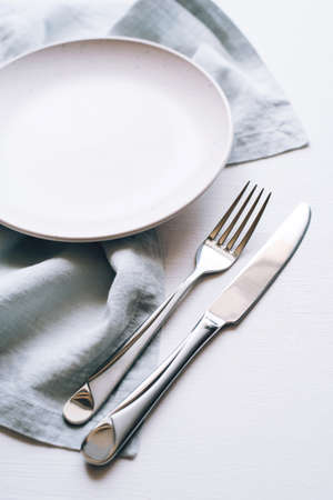 An empty plate and Cutlery on a white table. Top view. 免版税图像